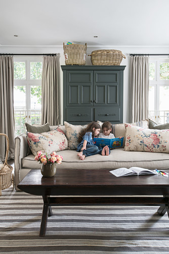 Two children reading on sofa with scatter cushions, dark cupboard flanked by windows and wooden coffee table in foreground
