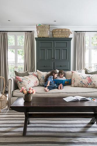 Zwei lesende Kinder auf Polstersofa mit Kissen, dunkler Schrank zwischen Fenstern, im Vordergrund Couchtisch aus Holz