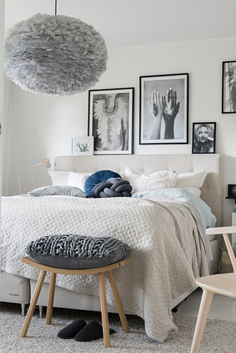 Beige and grey bedroom with black-and-white photos above bed