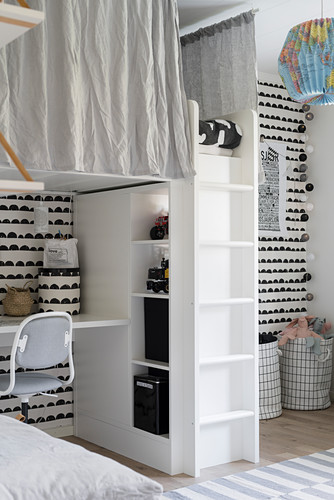 Loft bed above desk and shelving in child's bedroom with black-and-white wall