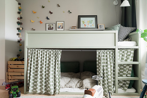 Loft bed with curtains screening cosy den below in child's bedroom