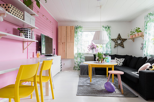 Pink wall in colourful living room with desk