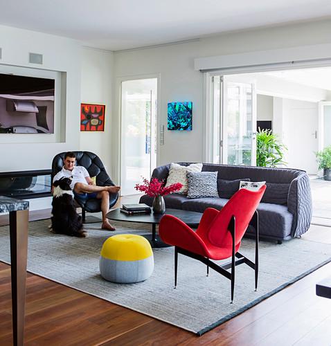Sitzmöbel, Coffeetable und Mann mit Hund im Wohnzimmer