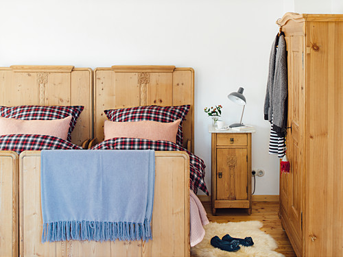 A rustic wooden bed with checked bedclothes, a bedside table and a wardrobe