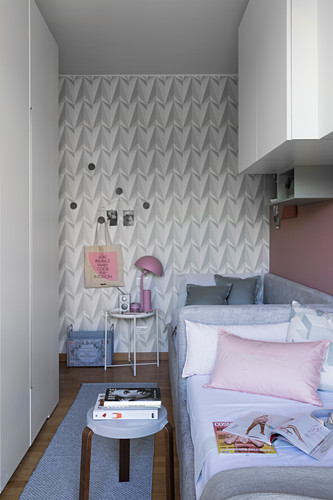 Two daybeds, side table and cupboards in narrow sibling's bedroom