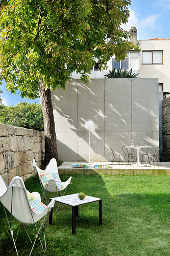 Classic chairs and side table on lawn in garden with terrace in background