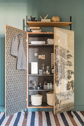 Bathroom utensils in old, refurbished wardrobe covered with vintage-style wallpaper