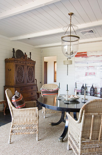 Wicker chairs at round table in dining room with wood-panelled ceiling