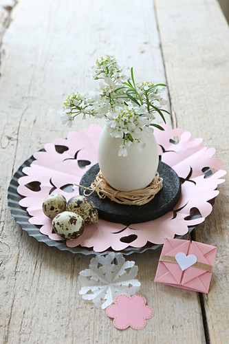 Easter arrangement of duck egg used as vase for small white flowers and origami envelop