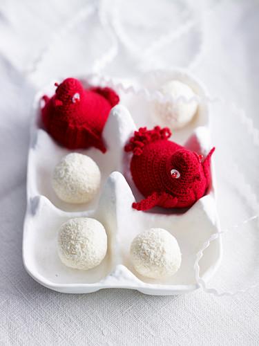 Gehäkelte rote Vögelchen und Trüffelpralinen in weißem Eierkarton