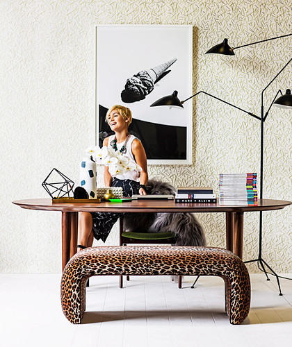 Blonde woman behind oval dining table, multi-arm floor lamp and leopard-look bench