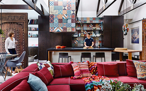 Red upholstery set with pillows, kitchen island, Moroccan encaustic tiles and antique, Moroccan door as a room divider, woman and man in the background