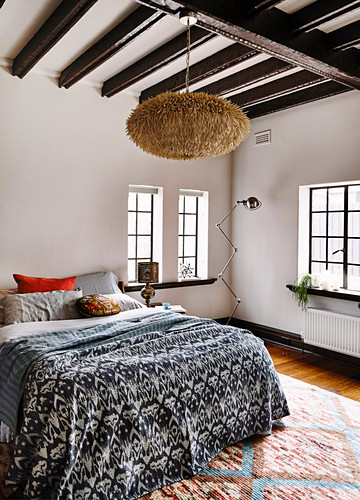 Double bed with bedspread, Moroccan lamp in the bedroom with dark beams