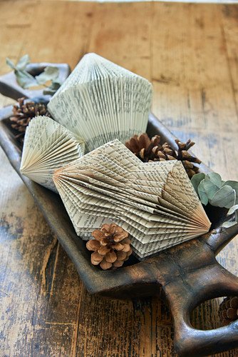 Prism-shaped Christmas decorations made from folded book pages and pine cones in wooden dish