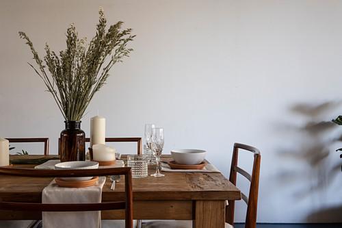 Gedeckter Holztisch mit Kerze und Getreideähren in Apothekerflasche