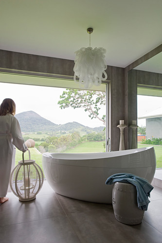 Free-standing oval bathtub in modern bathroom with panoramic windows