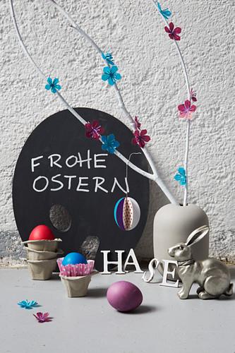 Zweige mit Papierblüten dekoriert in einer Vase, Osterhase und Ostereier im Eierkarton