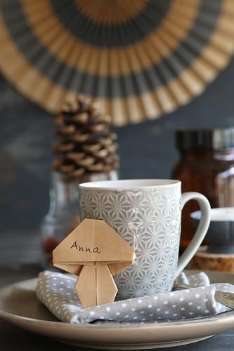 Origami mushroom name tag leaning against mug
