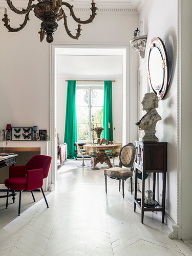 Bust on console table below mirror on wall and red upholstered chair in anteroom