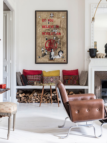 Cushions on bench with firewood stacked below next to fireplace and leather armchair in living room