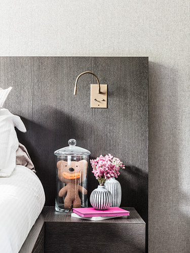 Teddy in sweet jar and vase of flowers on bedside cabinet