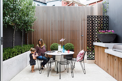 Mother and daughter on the courtyard terrace with outdoor kitchen
