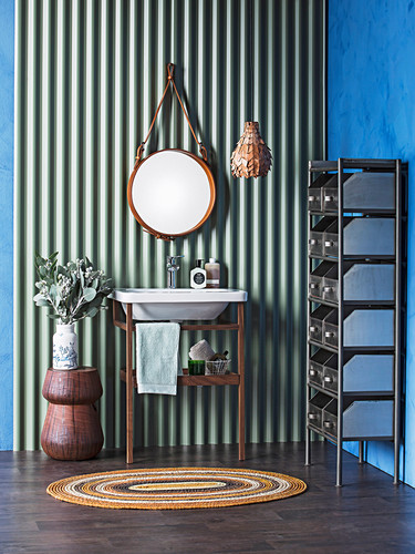 Vanity stand and round mirror on corrugated iron panel, metal shelf on the side with school baths on a blue wall