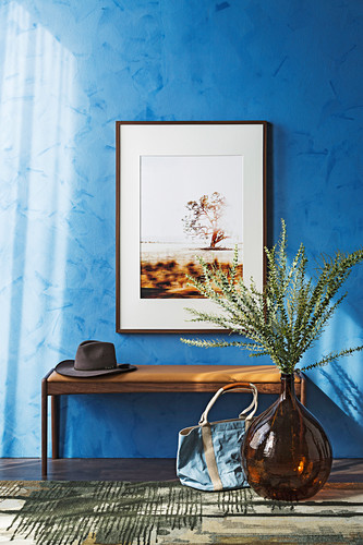 Bench with hat, picture on blue wall above, balloon vase with branch of leaves in the hallway