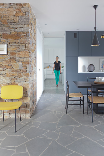 Open-plan interior with stone wall and dining area; woman in background