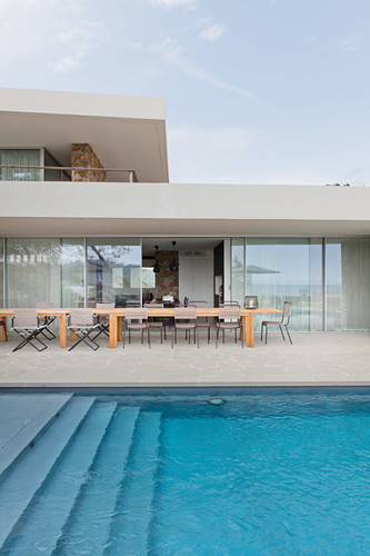 View across pool to long wooden table on stone-flagged terrace with glass sliding doors leading into house
