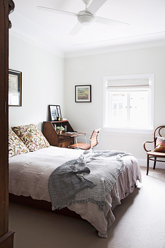 Glance into the bedroom with double bed and antique secretary