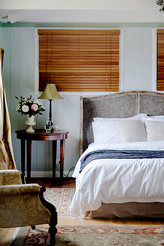 Double bed with headboard and round side table in front of window in bedroom