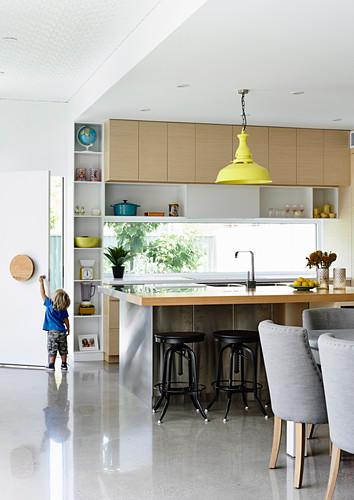 Bright, open kitchen with counter and polished concrete floor, in the back and toddler