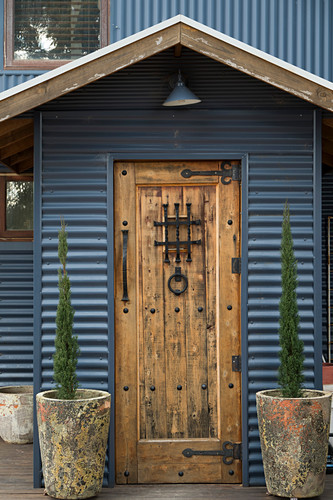 Rustic wooden door with metal fittings in corrugated metal wall of house