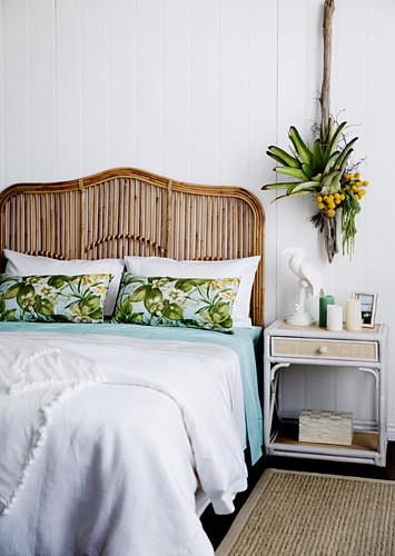 Rattanbett mit Betthaupt, Nachttisch und Pflanzendekoration im Schlafzimmer