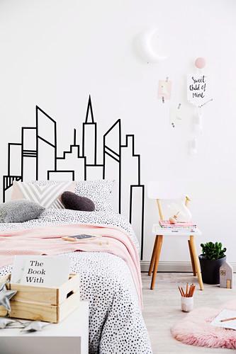 DIY-Skyline als Betthaupt im Schlafzimmer mit rosa Akzenten