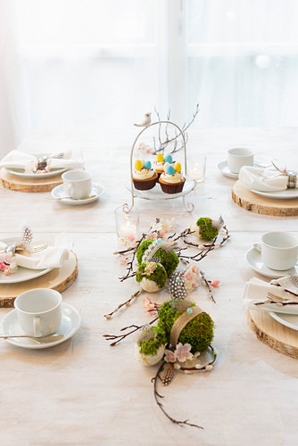 Handmade concrete Easter eggs wrapped in moss on set coffee table