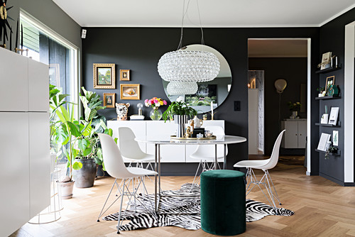 Delicate dining table and classic chairs on zebra-skin rug, green pouffe and white sideboards in interior with dark walls