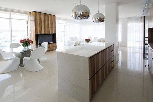 Marble kitchen counter, white designer chairs around glass table and TV cabinet in open-plan interior