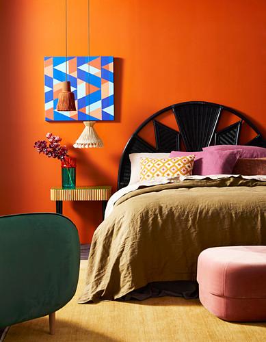 Doppelbett mit Betthaupt und Nachttisch vor orangefarbener Wand mit Bild