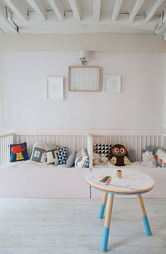Twin cots positioned end to end in bright nursery