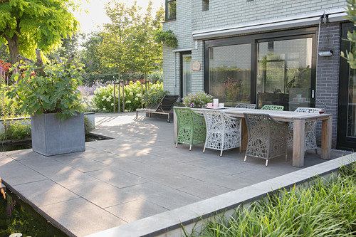 Wooden table and designer chairs on terrace with concrete flags