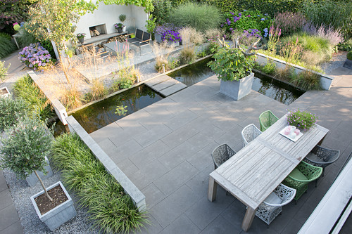 Wooden table and designer chairs on terrace with concrete flags surrounded by L-shaped pond