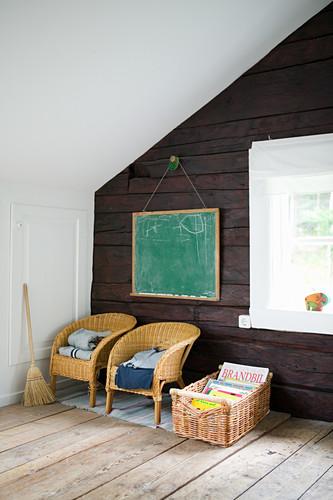 Two children's chairs below chalkboard on rustic wooden wall