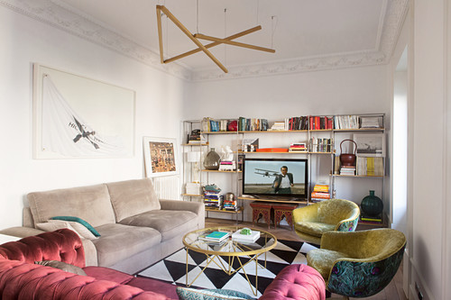 Various upholstered furnishings and TV on shelving in living room