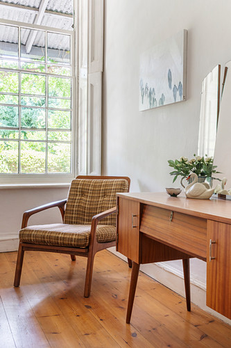 Retro dressing table and upholstered armchair in corner of room