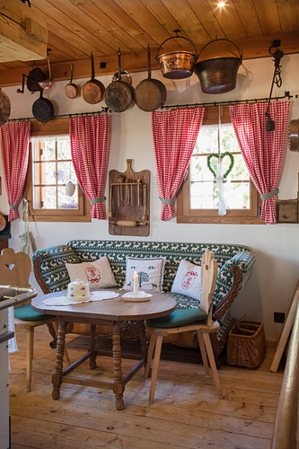 Two-seater sofa with wooden table and chairs in traditional farmhouse parlour