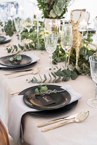 Table festively set for Christmas with eucalyptus branches