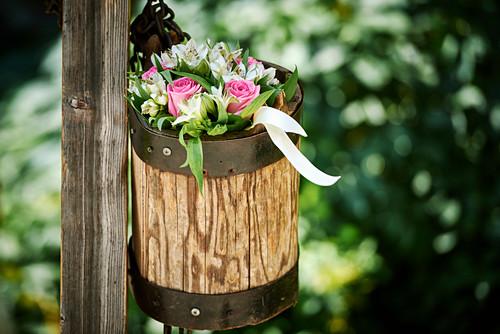 Bouquet in wooden pot on wooden pole in garden