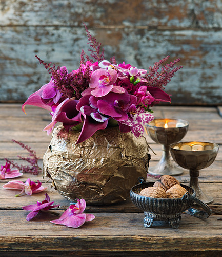 Moth orchids and astilbes in golden bowl